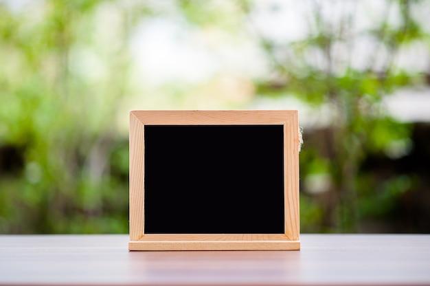 O giz vazio no assoalho de madeira acima tem o sol e o fundo verde borrados.