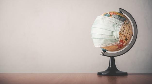 O globo está coberto com uma máscara no chão de madeira. o conceito é colocar uma máscara para parar o vírus covid-19.