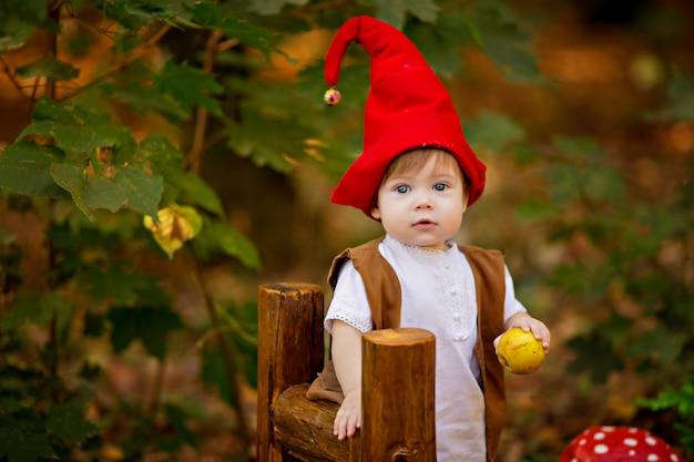 O gnomo feliz da floresta das fadas brinca e caminha na floresta, coleta e come deliciosas maçãs