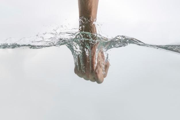 O golpe de ataque de mão de punho masculino através da superfície da água, movimento de poder de força