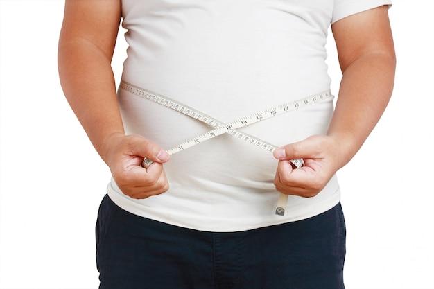 O gordo, a barriga é muito grande, de pé usando a fita métrica na cintura