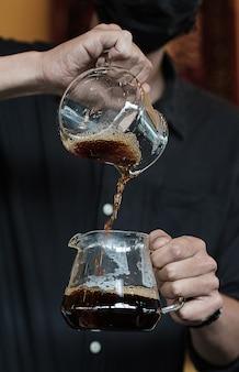 O gotejamento do café flui para outra jarra.