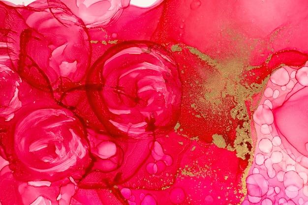 O gradiente de tinta aquarela vermelha abstrata cai com glitter dourado