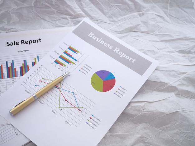O gráfico de papel de negócios e caneta colocar no lado esquerdo