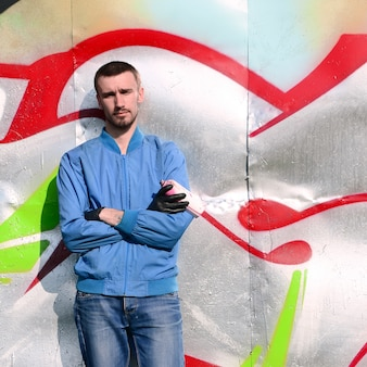 O grafiteiro com poses de lata de spray