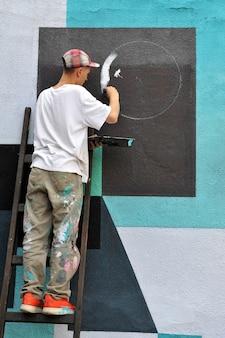 O grafiteiro pinta grafite colorido em uma parede de concreto.