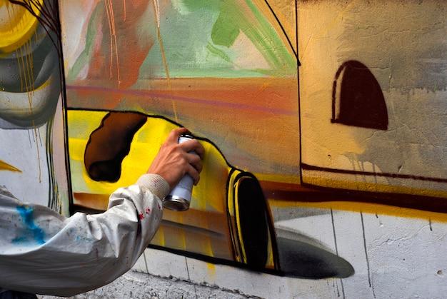 O grafiteiro pinta grafites coloridos em uma parede de concreto. arte moderna, conceito urbano.