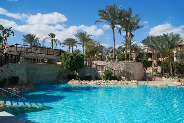 O grand hotel com palmeiras e piscina no verão