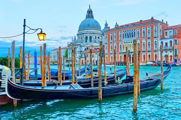 O grande canal com gôndolas atracadas em veneza no início da noite, itália