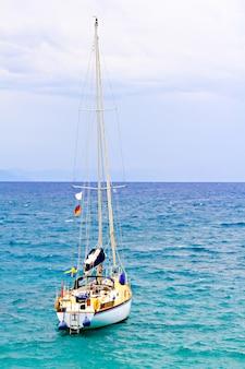 O grande e belo iate no mar azul-claro