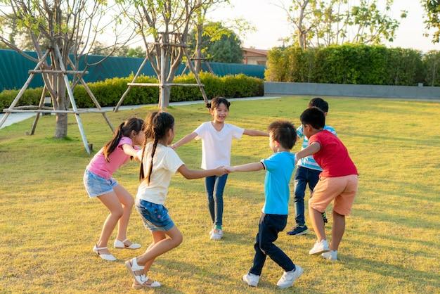 O grande grupo de jardim de infância de sorriso asiático feliz caçoa os amigos que guardam as mãos que jogam e que dançam o roundelay e estão no círculo no parque na grama verde no dia ensolarado de verão.