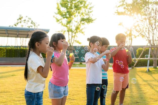 O grande grupo de jardim de infância de sorriso asiático feliz caçoa os amigos que jogam bolhas de sopro junto no parque na grama verde no dia de verão ensolarado.