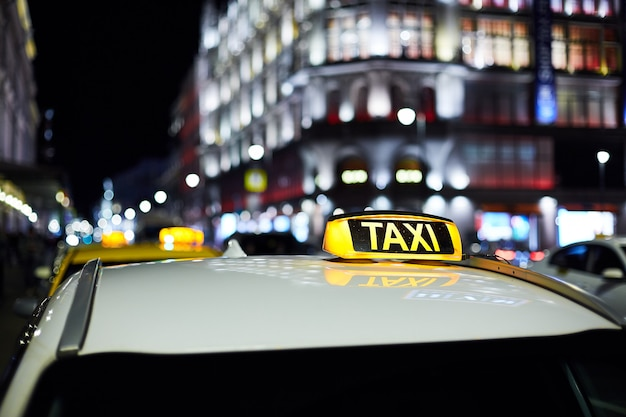 O grande sinal de táxi na cidade da noite