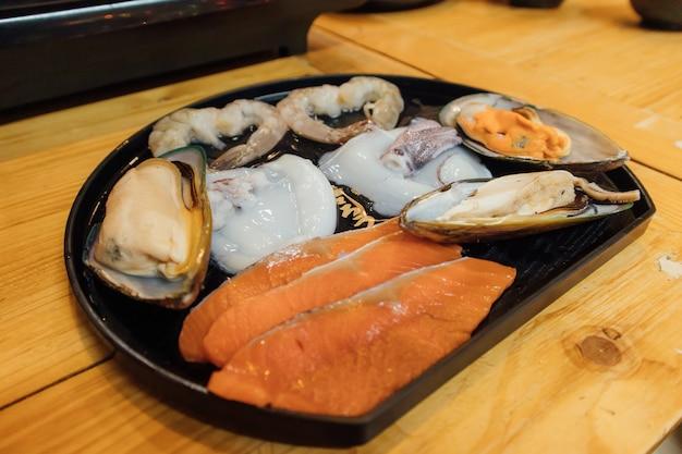 O grupo cru fresco do marisco serviu no estilo do restaurante do shabu.