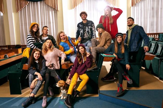 O grupo de alunos alegres e felizes sentados em uma sala de aula antes da aula