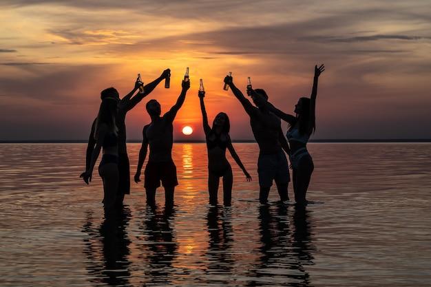 O grupo de amigos em pé sobre a água fazendo vivas contra o pôr do sol