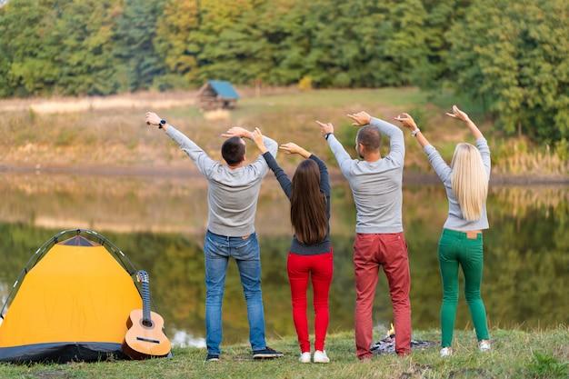 O grupo de amigos felizes com guitarra, se divertindo ao ar livre, dançando levanta as mãos perto do lago no fundo do parque o céu bonito. diversão em camping