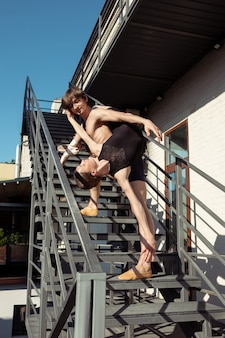 O grupo de bailarinos modernos realizando nas escadas da cidade