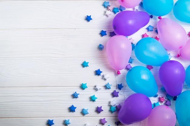 O grupo de balões coloridos do partido com papel stars no fundo de madeira branco. flat lay estilo com copyspace