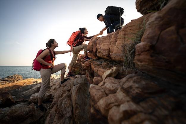 O grupo de caminhadas de ásia ajuda-se a silhueta nas montanhas com a luz solar.