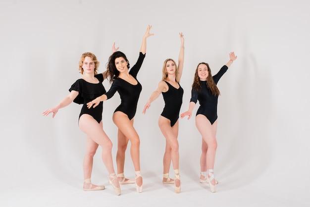 O grupo de dançarinos de balé moderno em traje preto em estúdio branco