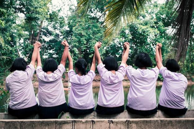 O grupo de estudantes de uniforme de mãos dadas juntos feliz.conceito de melhores amigos
