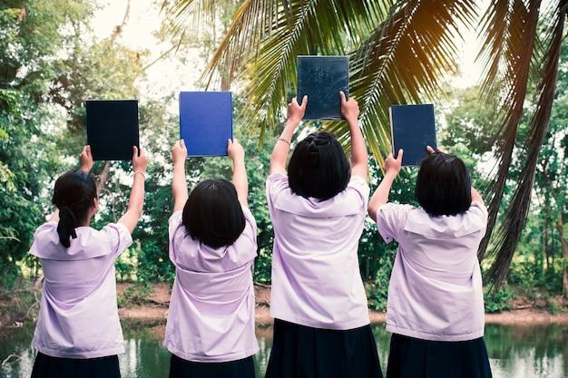 O grupo de estudantes de uniforme segurando o livro. conceito de melhores amigos