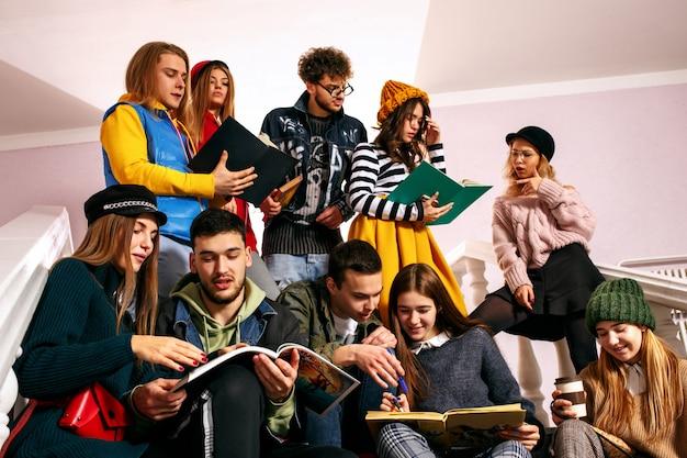 O grupo de estudantes felizes alegres, sentado em uma sala de aula antes da lição