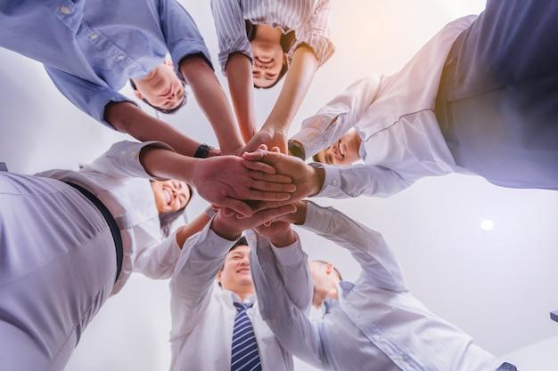 O grupo de executivos junta as mãos no escritório. visão de baixo ângulo.