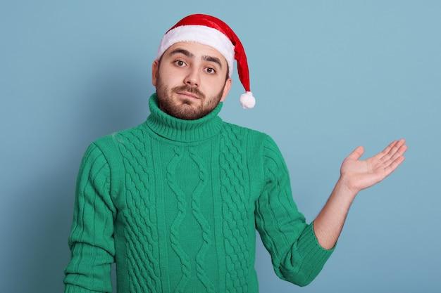 O grupo de homem barbudo bonito veste a camisola verde quente do inverno e o chapéu do natal, levantando isolado sobre o azul, tendo intrigado a expressão facial.