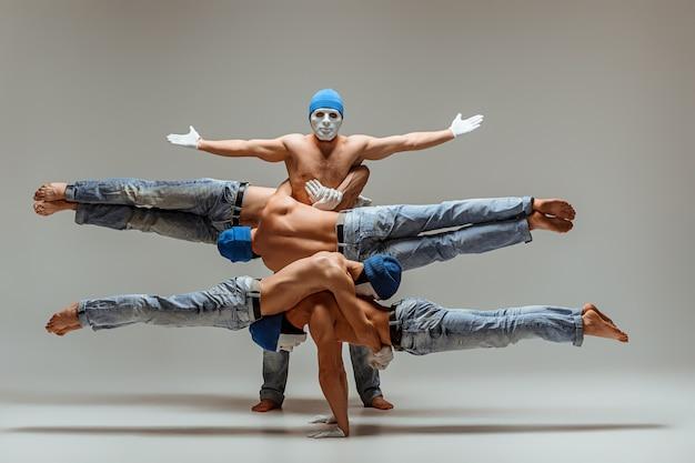 O grupo de homens caucasianos acrobáticos ginásticos em pose de equilíbrio