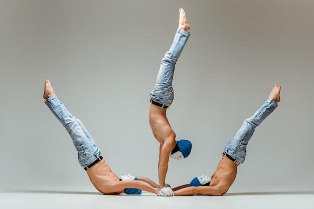 O grupo de homens caucasianos acrobáticos ginásticos na pose de equilíbrio