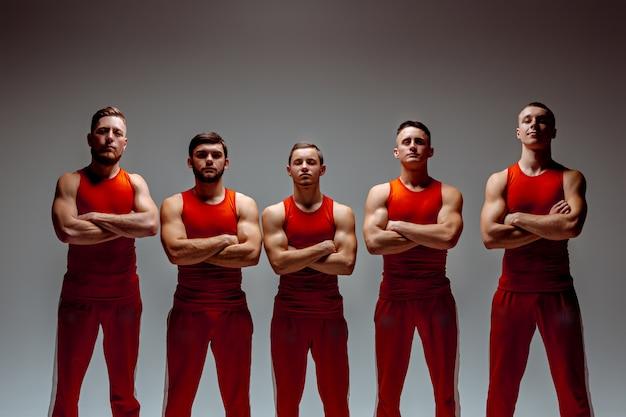 O grupo de homens caucasianos acrobáticos ginásticos