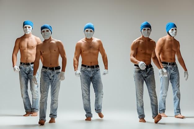 O grupo de homens caucasianos em máscaras brancas e chapéus, jeans