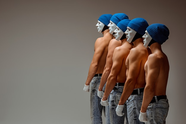 O grupo de homens caucasianos em máscaras e chapéus brancos, jeans