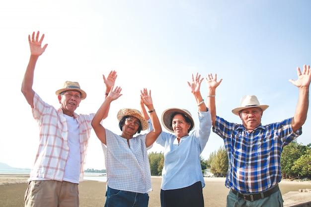 O grupo de idosos de homens e mulheres na ásia visitou o mar. levante os dois braços com prazer.