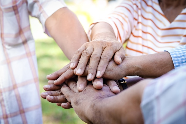 O grupo de idosos se dá as mãos tenha uma vida feliz após a aposentadoria. conceito de comunidade de idosos