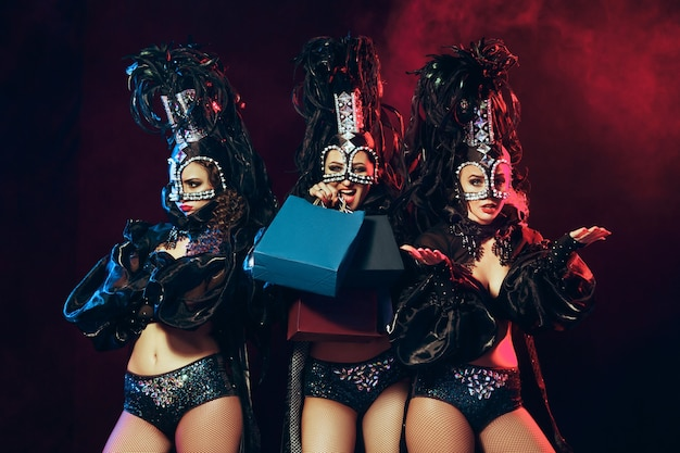 O grupo de jovens felizes e sorridentes lindas dançarinas com vestidos de carnaval posando com sacolas de compras no fundo preto do estúdio