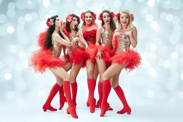 O grupo de jovens felizes e sorridentes lindas dançarinas com vestidos de carnaval posando em fundo azul do estúdio