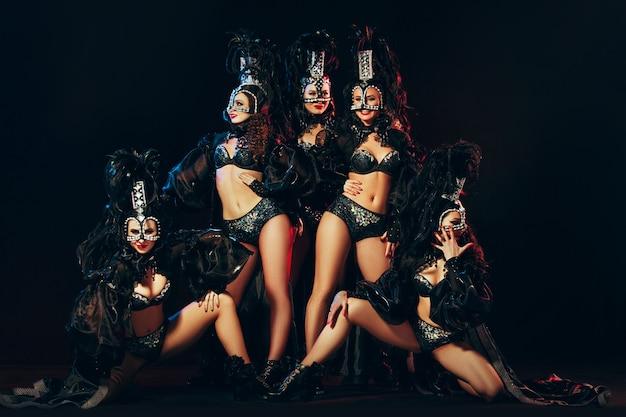 O grupo de jovens felizes e sorridentes lindas dançarinas com vestidos de carnaval