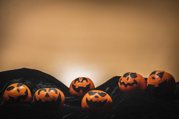 O grupo de laranjas enfrenta a pintura com o assustador no dia do partido de dia das bruxas com fundo alaranjado.