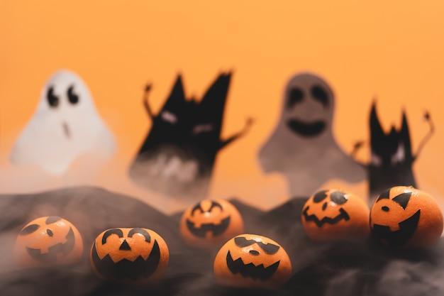O grupo de laranjas enfrenta a pintura com o assustador no dia do partido de dia das bruxas com mito.