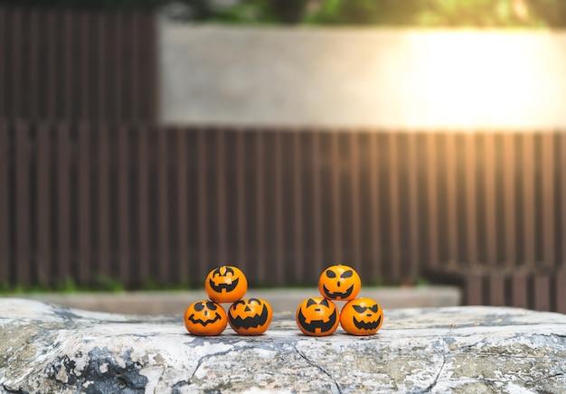 O grupo de laranjas enfrenta a pintura com o assustador no dia do partido do dia das bruxas no lugar do jardim.