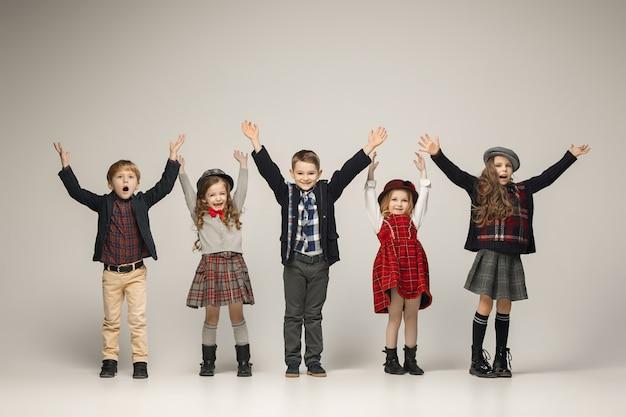 O grupo de lindas meninas e meninos em uma parede pastel