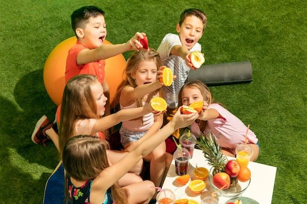 O grupo de meninos e meninas adolescentes sentados na grama verde do parque Foto gratuita