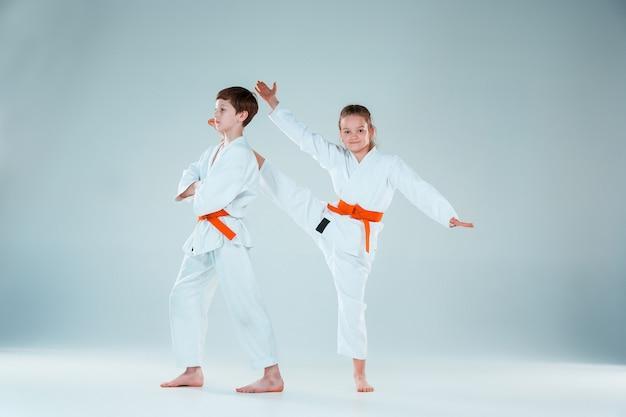 O grupo de meninos e meninas no treinamento de aikido na escola de artes marciais. estilo de vida saudável e conceito de esportes