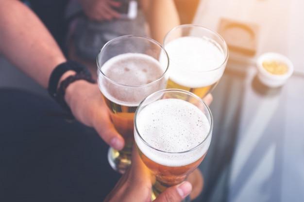 O grupo de pessoas bebendo cerveja e tilintar de copos no bar do terraço para celebração