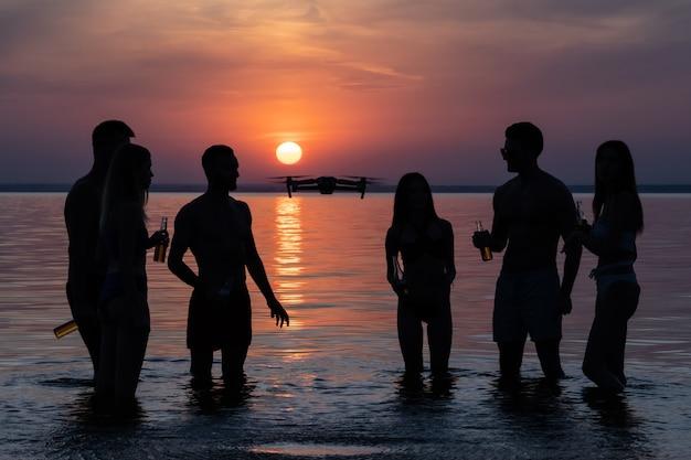O grupo de pessoas em pé na água contra o belo pôr do sol