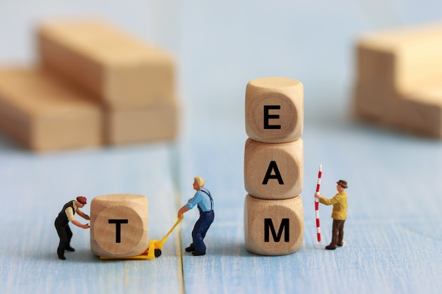 O grupo de povos diminutos monta o cubo de madeira, o apoio da equipe e o conceito da ajuda. conceito de trabalho em equipe de negócios.