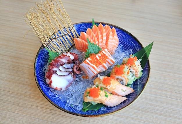 O grupo do sashimi serviu no gelo contra a tabela de madeira. comida japonesa.